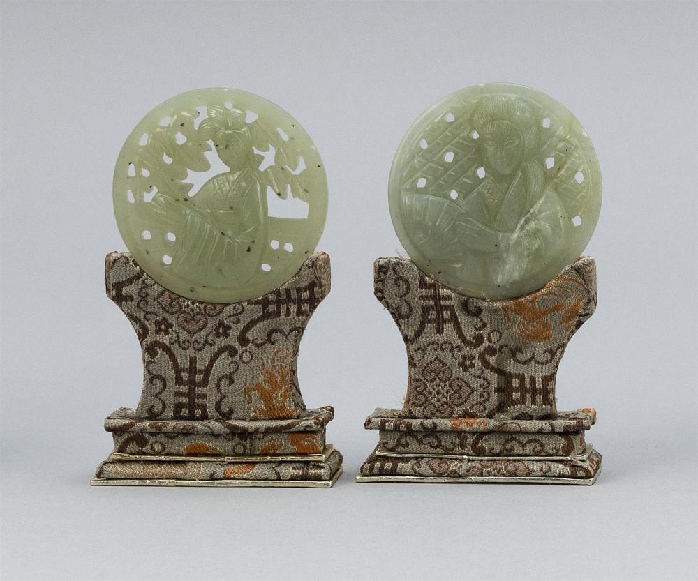 "TWO CHINESE LIGHT CELADON JADE PLAQUES Both carved with raised figural decoration. Diameters 2"". On brocade stands. Provenance: A pr..."