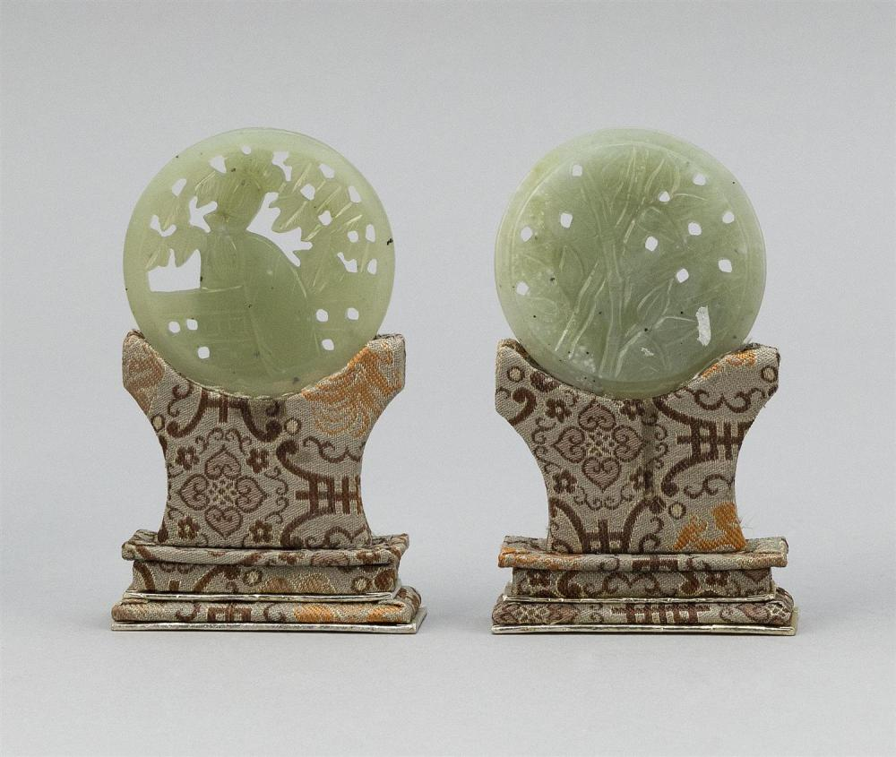 TWO CHINESE LIGHT CELADON JADE PLAQUES Both carved with raised figural decoration. Diameters 2