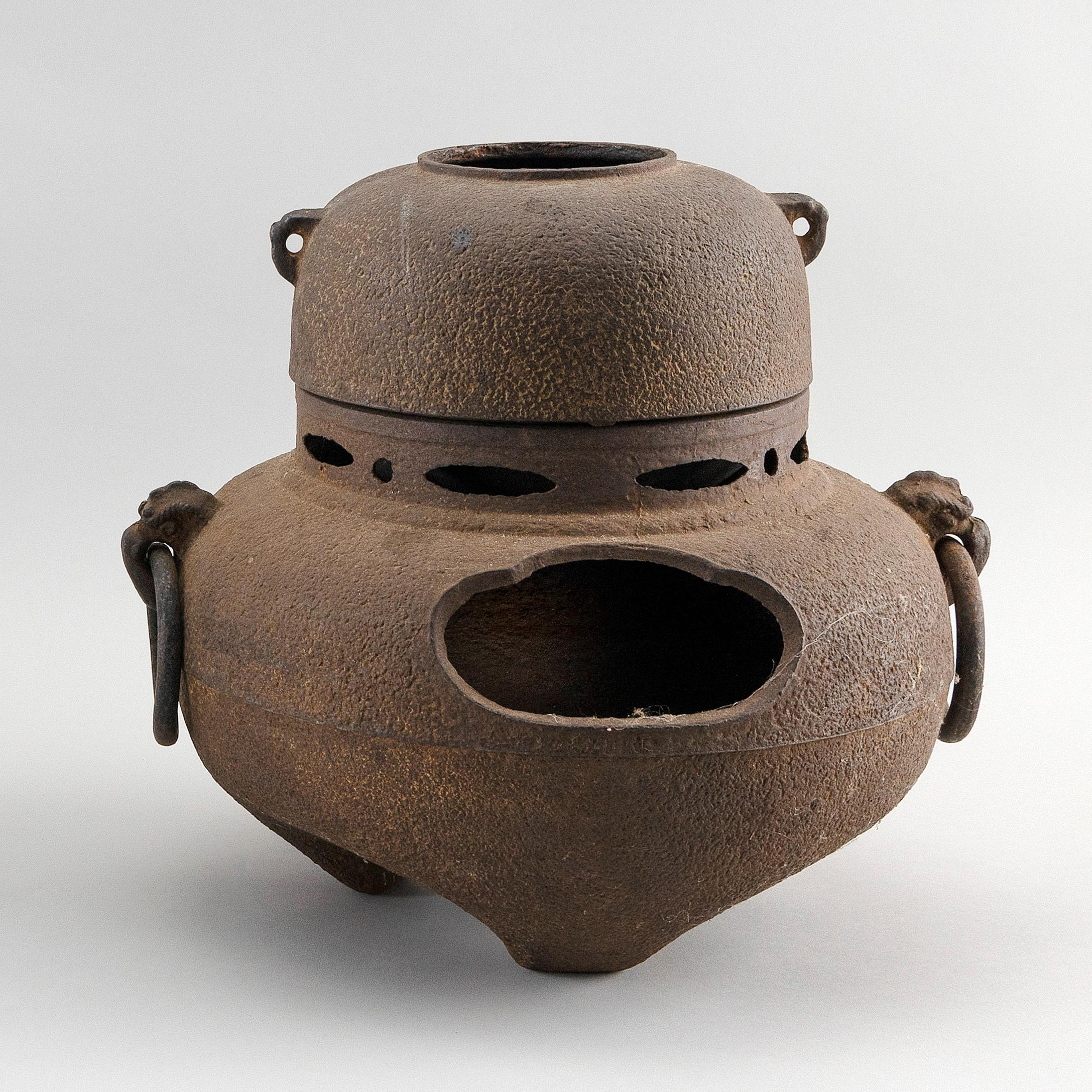 JAPANESE CAST IRON TWO-PIECE HIBACHI AND KETTLE FOR TEA CEREMONY Furo (hibachi base) in squat ovoid form with mask and ring handles...