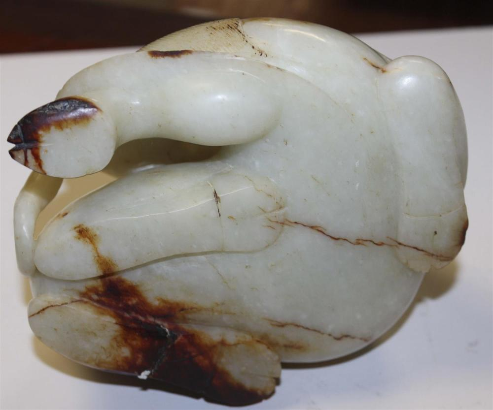 CHINESE CARVED WHITE AND RUSSET JADE CARVING OF A RECLINING CAMEL Fine integration of russet skin tones. Height 3.5