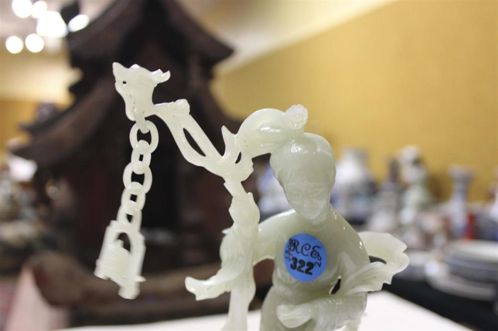 CHINESE CELADON JADE FIGURE GROUP A mother and child standing under a bird perched on a swing. Height 7.25