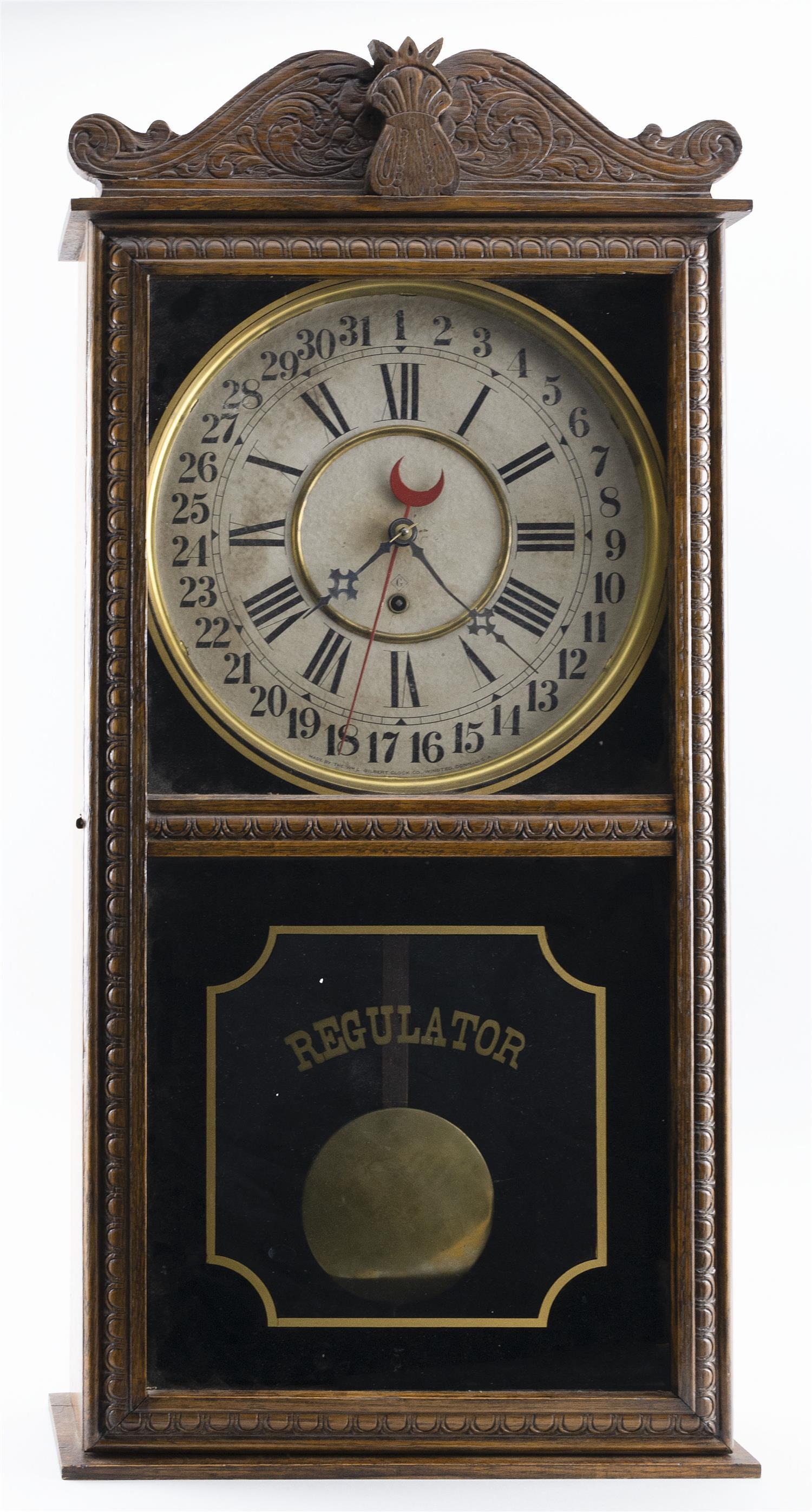 """GILBERT REGULATOR CALENDAR CLOCK Oak case with carved wheat design. Reverse-painted black and gold tablet. Height 32.75"""". Width 16""""...."""