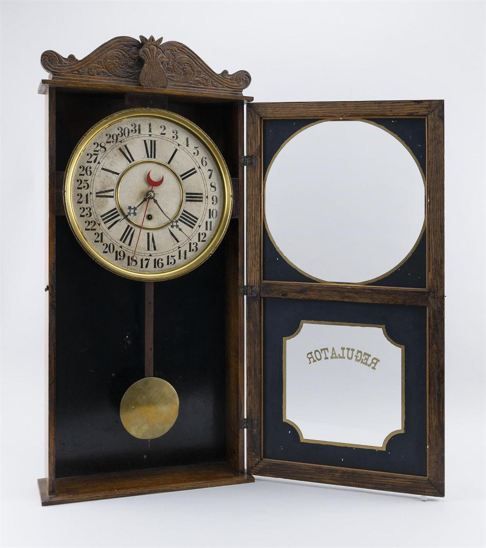 GILBERT REGULATOR CALENDAR CLOCK Oak case with carved wheat design. Reverse-painted black and gold tablet. Height 32.75
