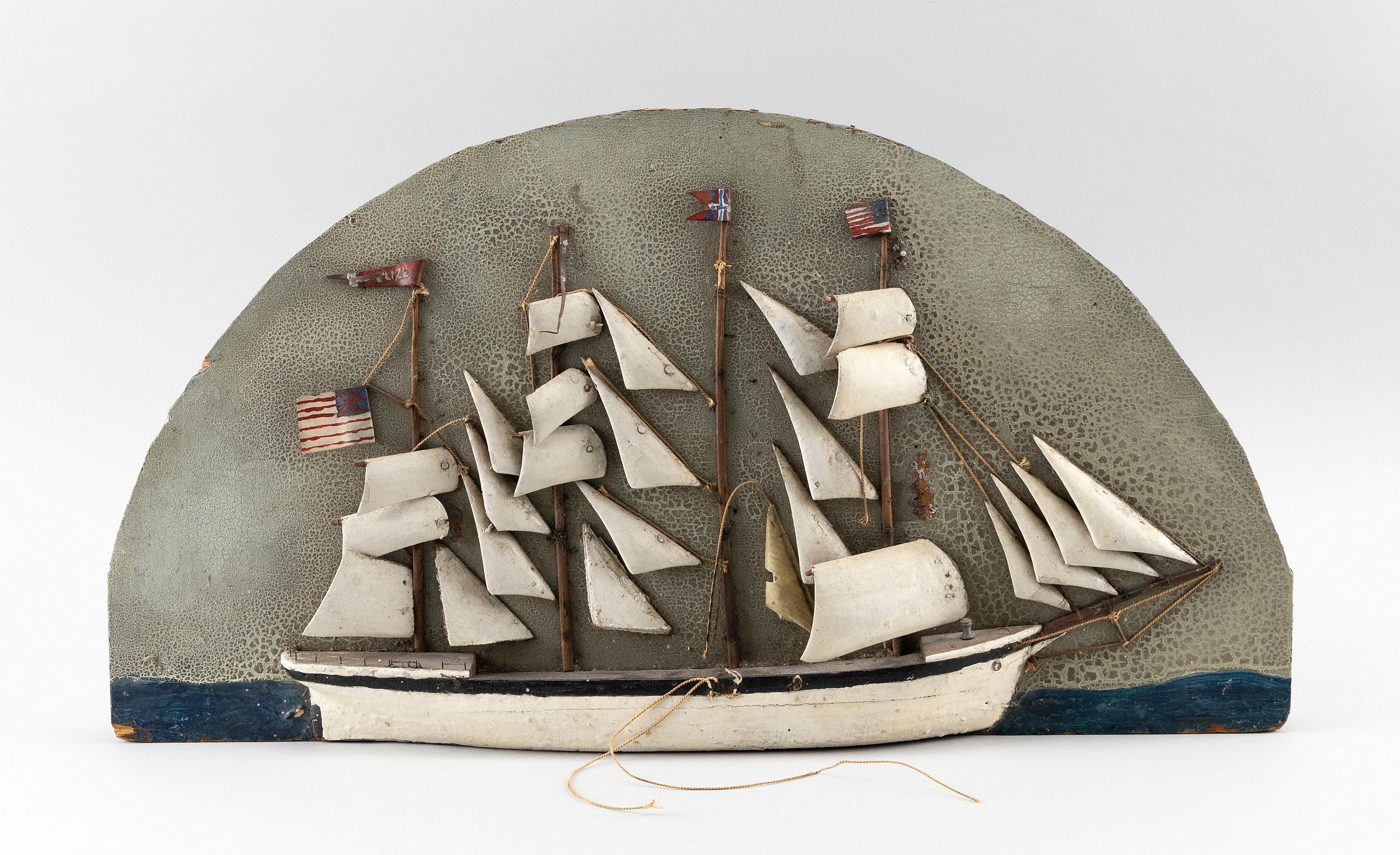 """DIORAMA OF A FOUR-MASTED SHIP With a black and white hull. Flying an American flag. Height 11.5"""". Length 21""""."""