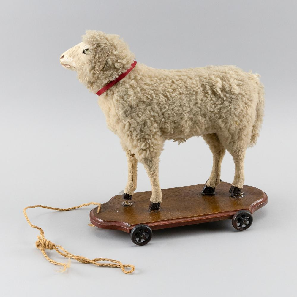 """SHEEP PULL TOY Composition sheep on a wooden base. Length 14""""."""