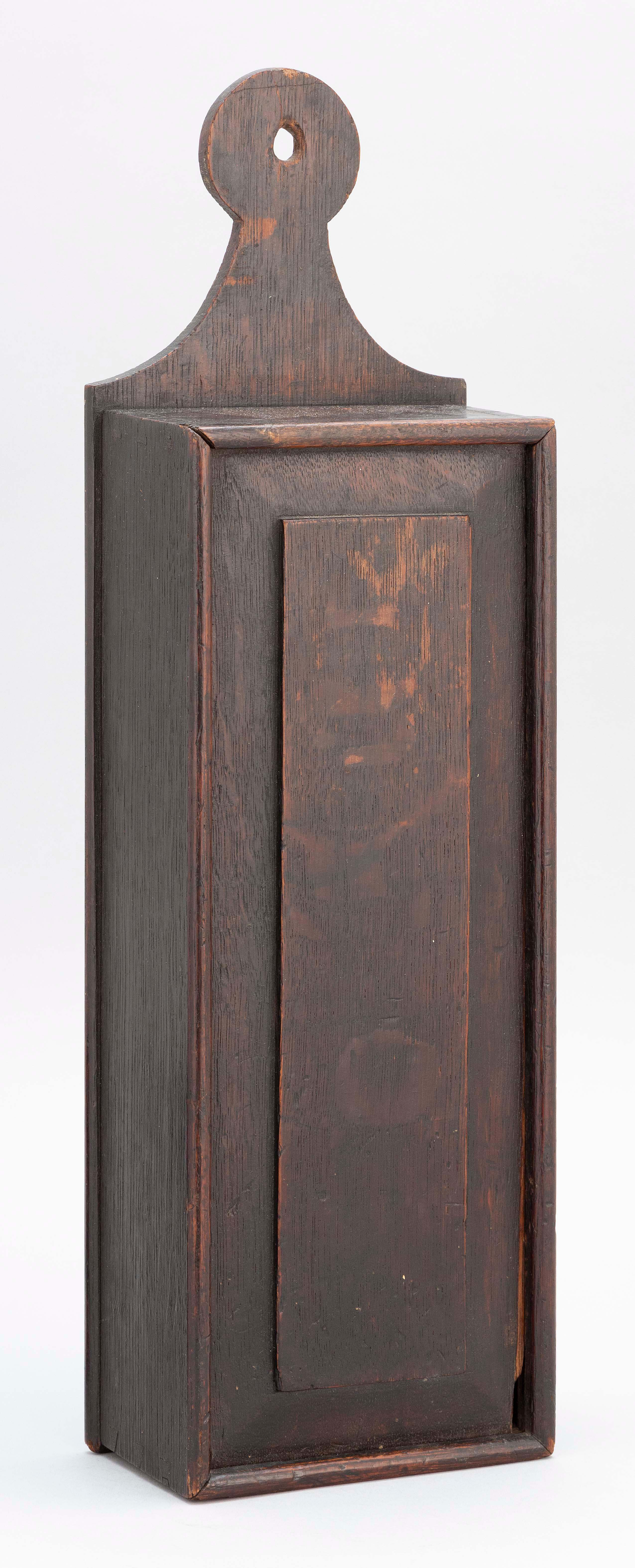 """OAK CANDLE BOX With dovetailed sides, sliding panel front and an old brown finish. Height 19.5"""". Width 6"""". Depth 3.25""""."""