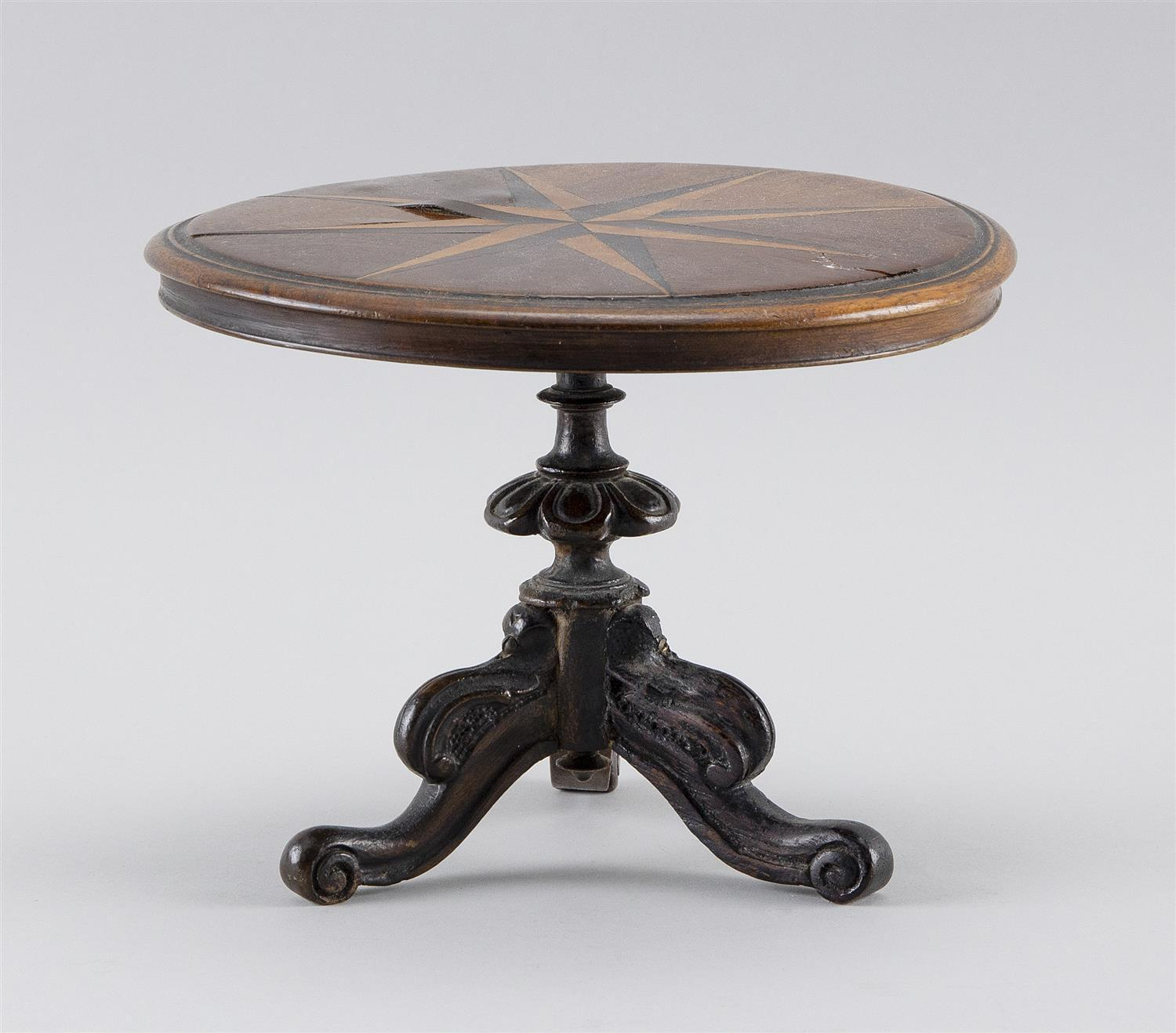 MINIATURE MAHOGANY TEA TABLE Circular molded-edge top inlaid with an eight-point star. Tripod base with floriform knop and three scr...