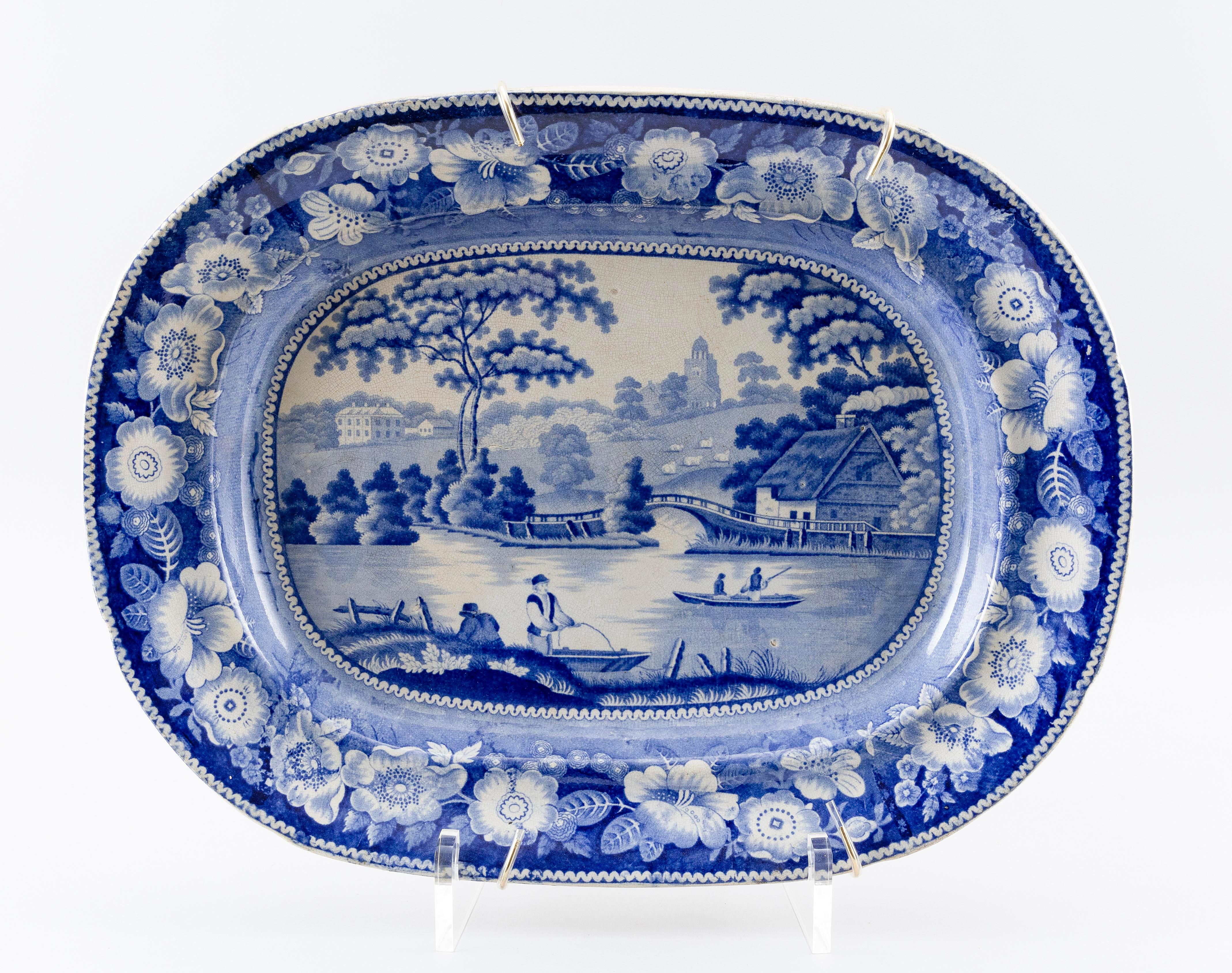 "BLUE AND WHITE TRANSFERWARE PLATTER Depicts the English countryside. Unmarked. Length 21""."