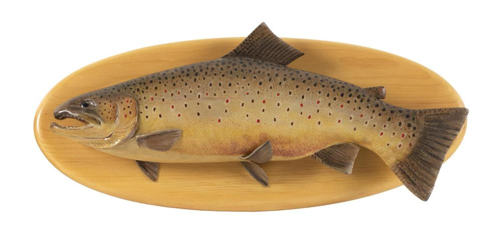"""MIKE BORRETT CARVED AND PAINTED WOODEN BROWN TROUT Mounted on an oval pine backboard. Trout length 19"""". Backboard length 20""""."""