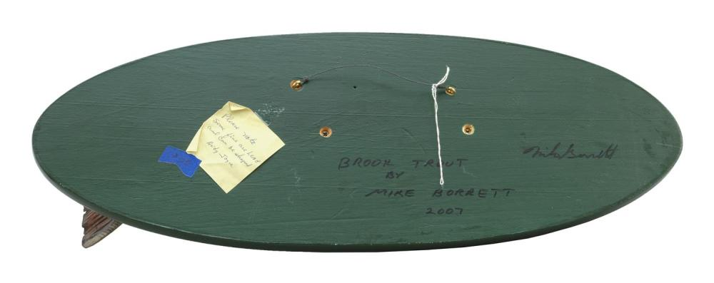 MIKE BORRETT CARVED AND PAINTED WOODEN BROOK TROUT Mounted on a green-painted oval backboard. Signed and dated on reverse
