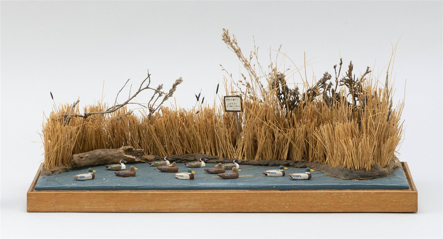 """WATERFOWL DIORAMA BY A.C. GOULD Depicts eleven miniature decoys in a pond. Height 6.5"""". Width 15"""". Depth 6""""."""