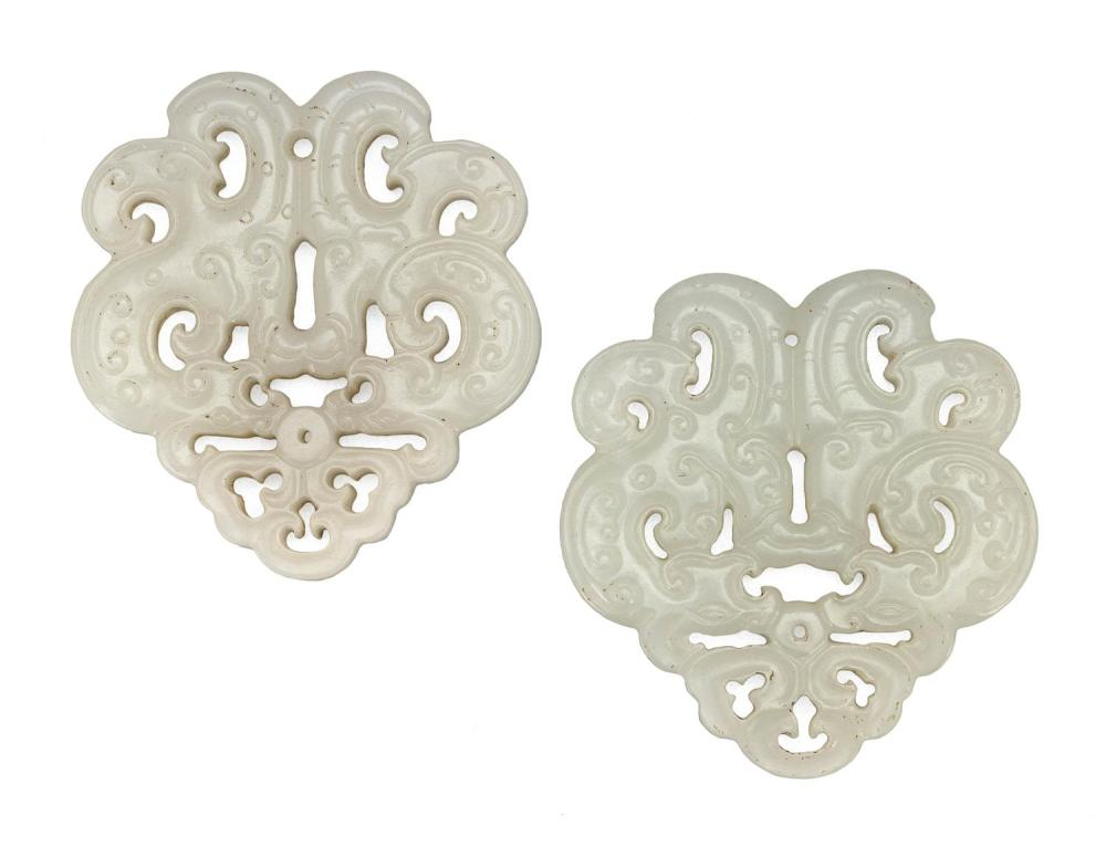 RARE PAIR OF PURE WHITE JADE PENDANTS Both in the form of two sinuous archaic-style dragons suspended from a ruyi finial, with the s...