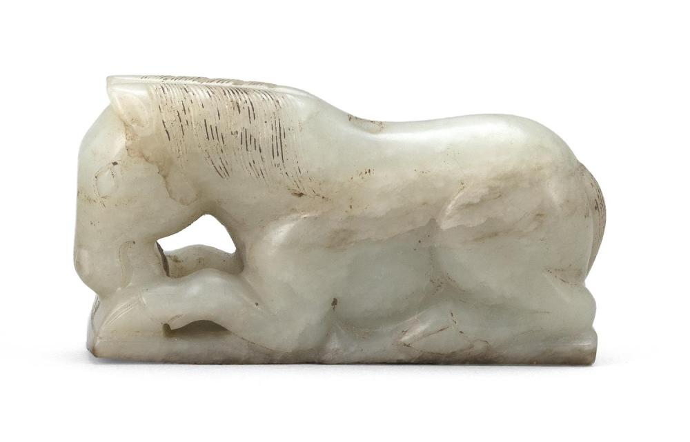 CELADON AND BROWN JADE CARVING OF A RECLINING HORSE With its front legs outstretched and head slightly lifted. A well-defined mane d...