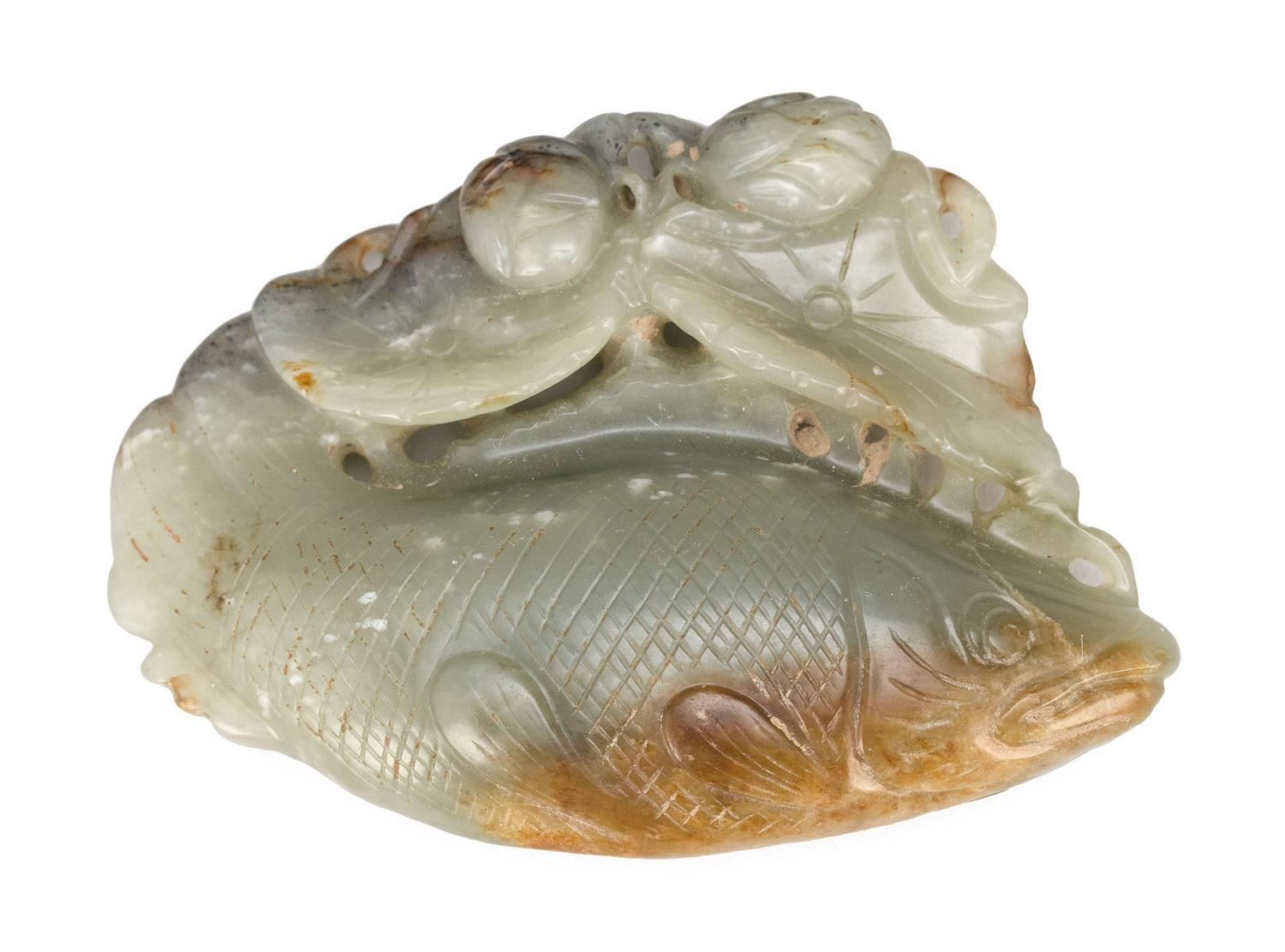 SAGE GREEN JADE CARVING OF A SOLITARY FISH Its tail is gently turned as it glides through shallow waters beneath lily pads and lotus...