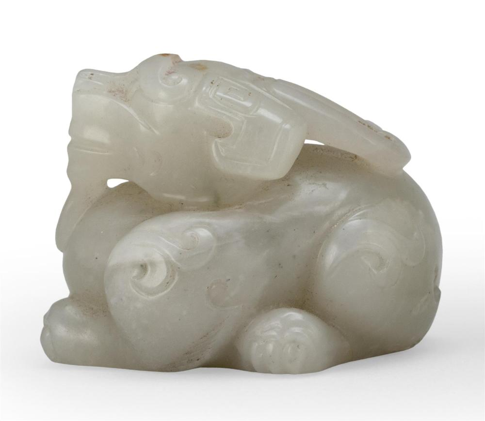 TRANSLUCENT GRAY JADE CARVING OF A TWO-HORNED QILIN Crouching, with its head raised, its bifurcated tail swept over its right leg, a...