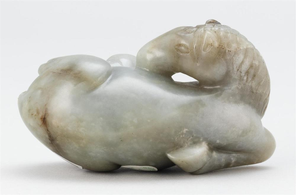 GRAY AND RUSSET JADE CARVING OF A RECUMBENT HORSE With its head turned back and appearing to roll over in a playful manner. Mane nea...
