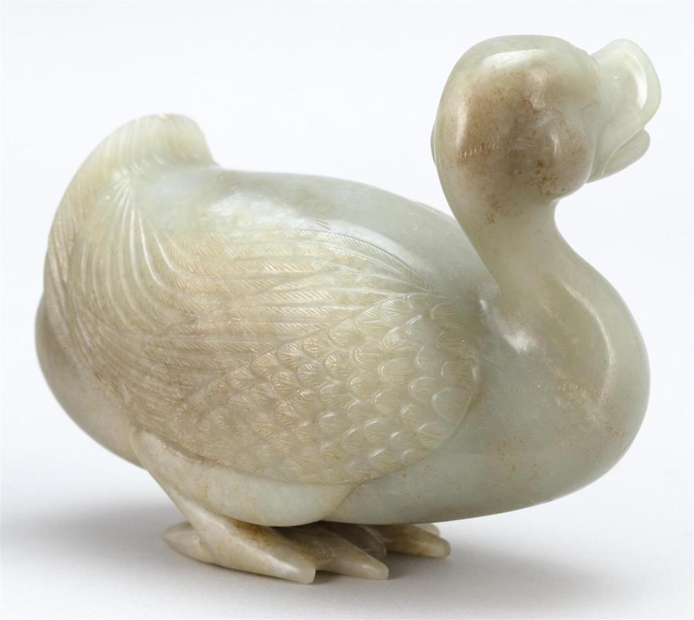 CELADON JADE BOULDER CARVING OF A GOOSE Standing with its head turned. Finely detailed featherwork. Highlighted with russet details....