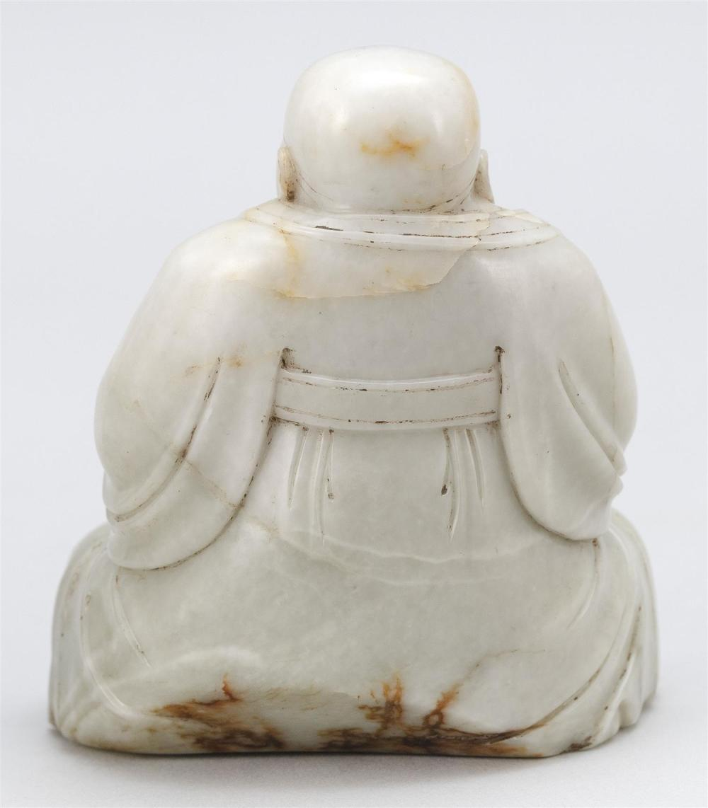 WHITE JADE CARVING OF A SEATED IMMORTAL Wearing an official's hat, a belted robe with voluminous sleeves, and loose trousers. Vaporo..
