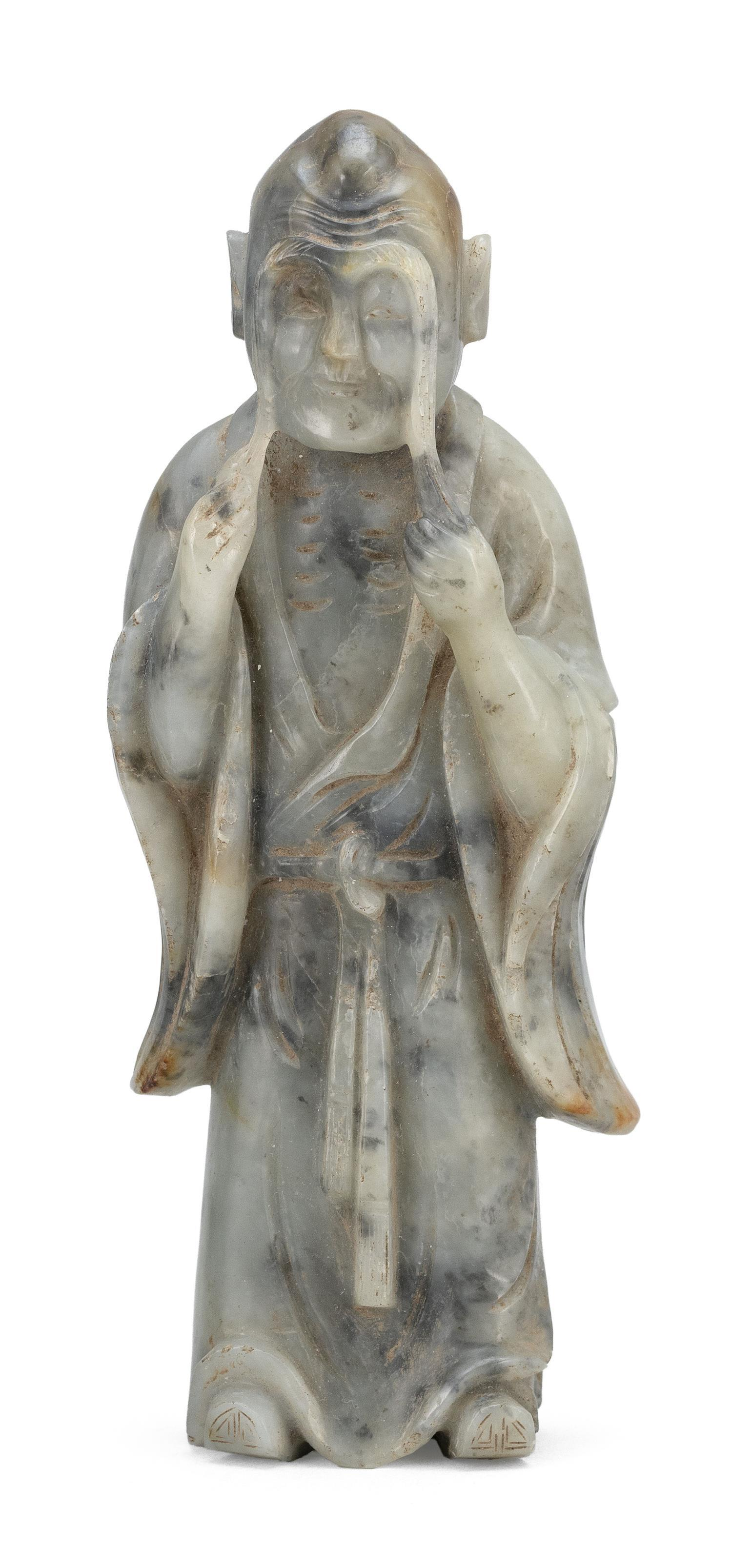 GRAY AND BLACK JADE CARVING OF THE LOHAN ZHANG MEI Wearing a long belted robe and standing while holding onto his enormous eyebrows....
