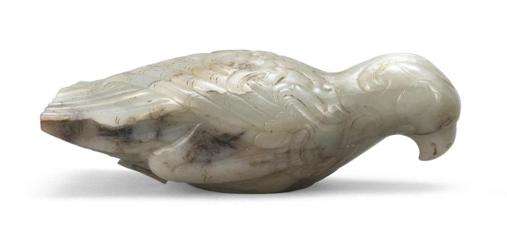 GRAY WHITE AND RUSSET JADE FINIAL In the form of a bird with folded wings, neatly incised tail feathers and carefully delineated fee...