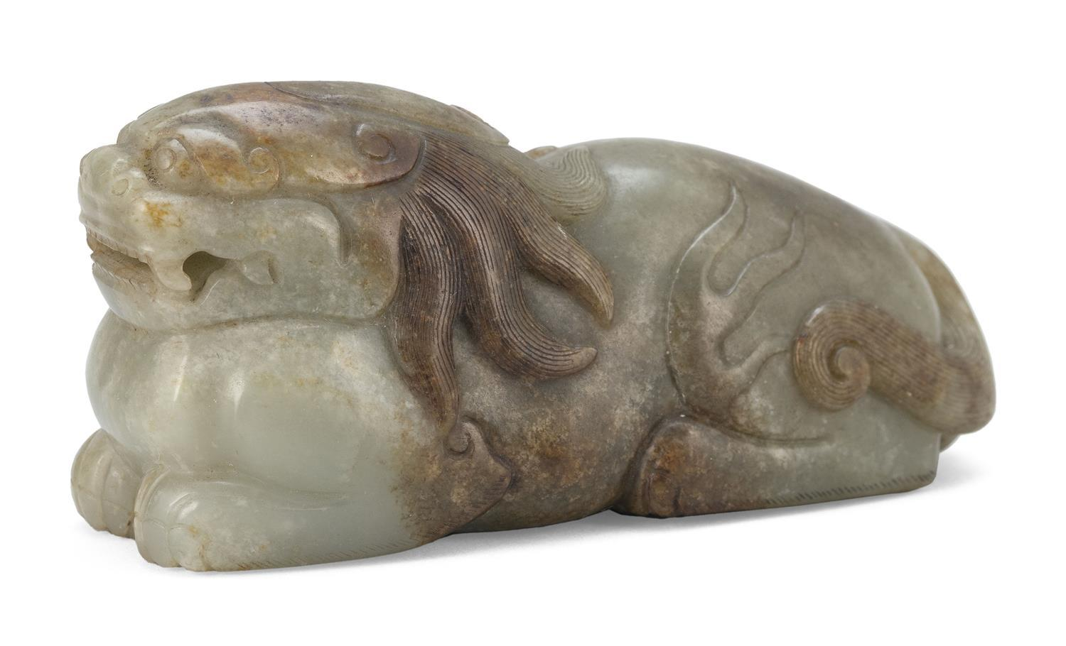 CELADON AND RUSSET JADE CARVING OF A QILIN Reclining and positioned straight forward. Boldy carved with open mouth, single horn, tra...