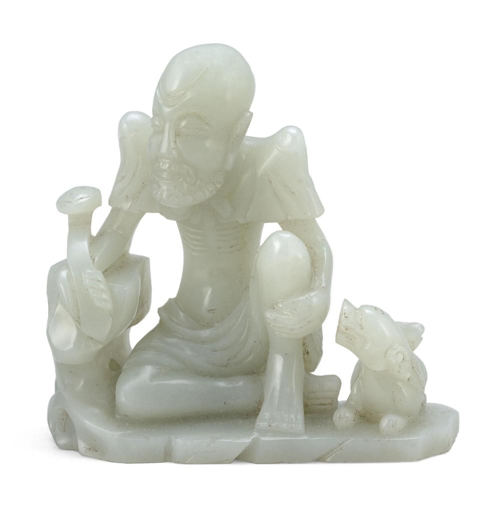 PURE CELADON JADE CARVING OF ARHAT Wearing a cloak tied with a ribbon while seated on a rockery base and holding a ruyi scepter, wai...