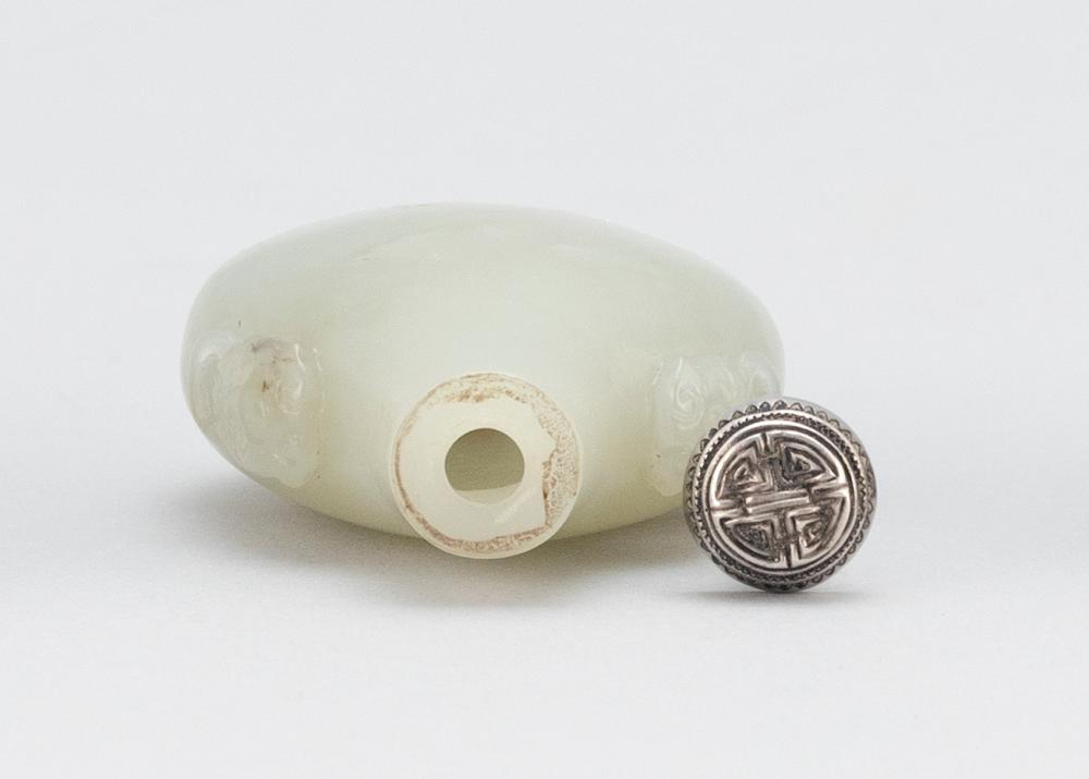CHINESE CELADON GREEN JADE SNUFF BOTTLE In flattened pear form with mask and mock ring handles at the shoulder. Height 2.1