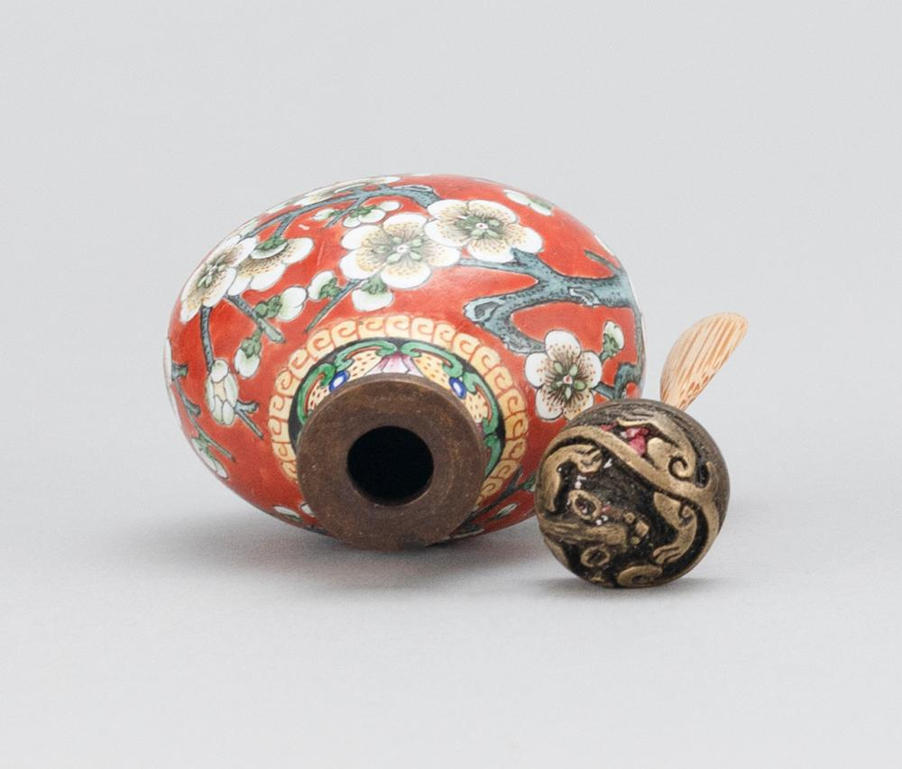 CHINESE BEIJING ENAMEL-ON-COPPER SNUFF BOTTLE In pear form, with a prunus design on a tomato red ground. Four-character Qilong mark...