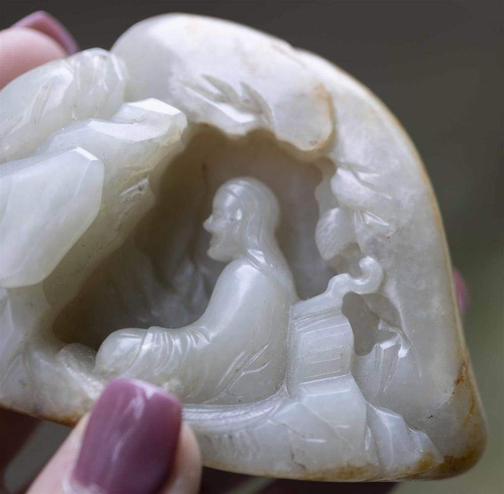 LARGE CELADON AND RUSSET-COLORED RIVER PEBBLE JADE CARVING In its near-original shape. Obverse carved with multiple layers to depict...