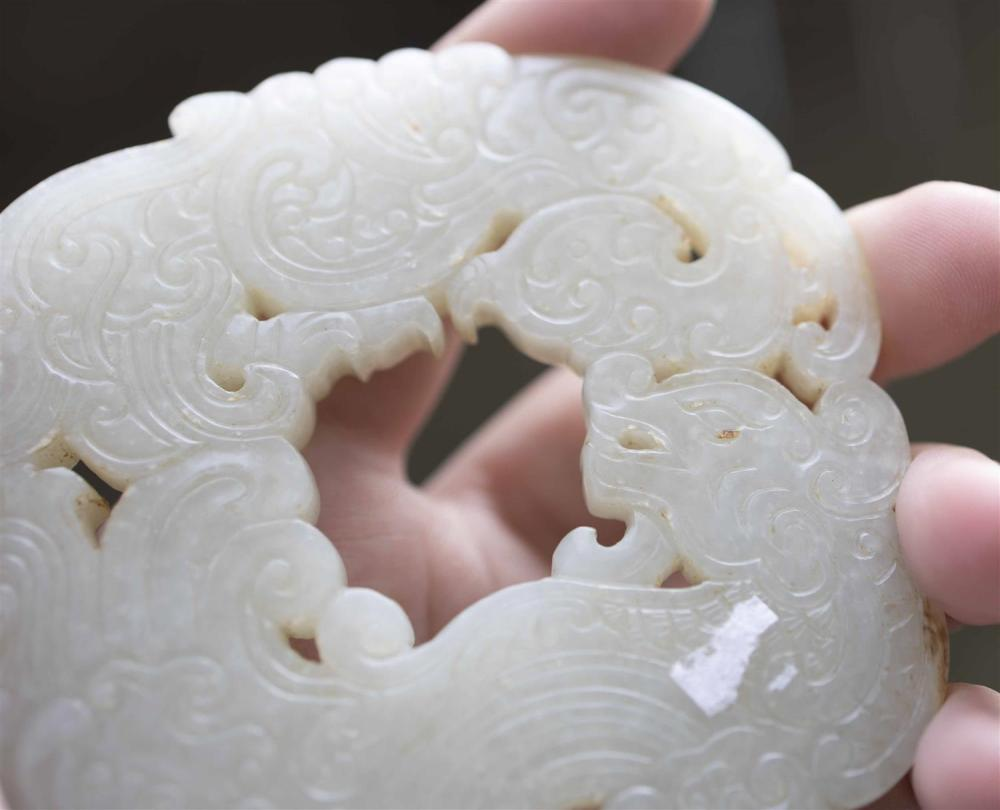 PALE CELADON JADE BI Carved with pierced phoenix and dragon motifs amongst archaic-style clouds. Slight russet inclusions. Possibly...