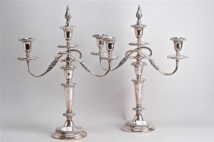 PAIR OF SILVER PLATED THREE-SOCLE CANDELABRA with ribbed decoration and flame finial. Heights 15¼