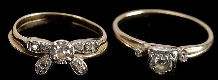 TWO DIAMOND AND YELLOW GOLD RINGS: one with diamond solitaire flanked by smaller diamonds and one with single diamond set with four...