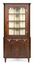 TWO-PART CORNER CUPBOARD In mahogany. Upper case with ogee molding over a single glazed twelve-panel door with tombstone arches. Low...