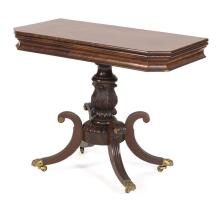 FEDERAL CARD TABLE In mahogany. Cut-corner top set on a concave molded skirt. Beautifully carved pedestal with acanthus design. Four...