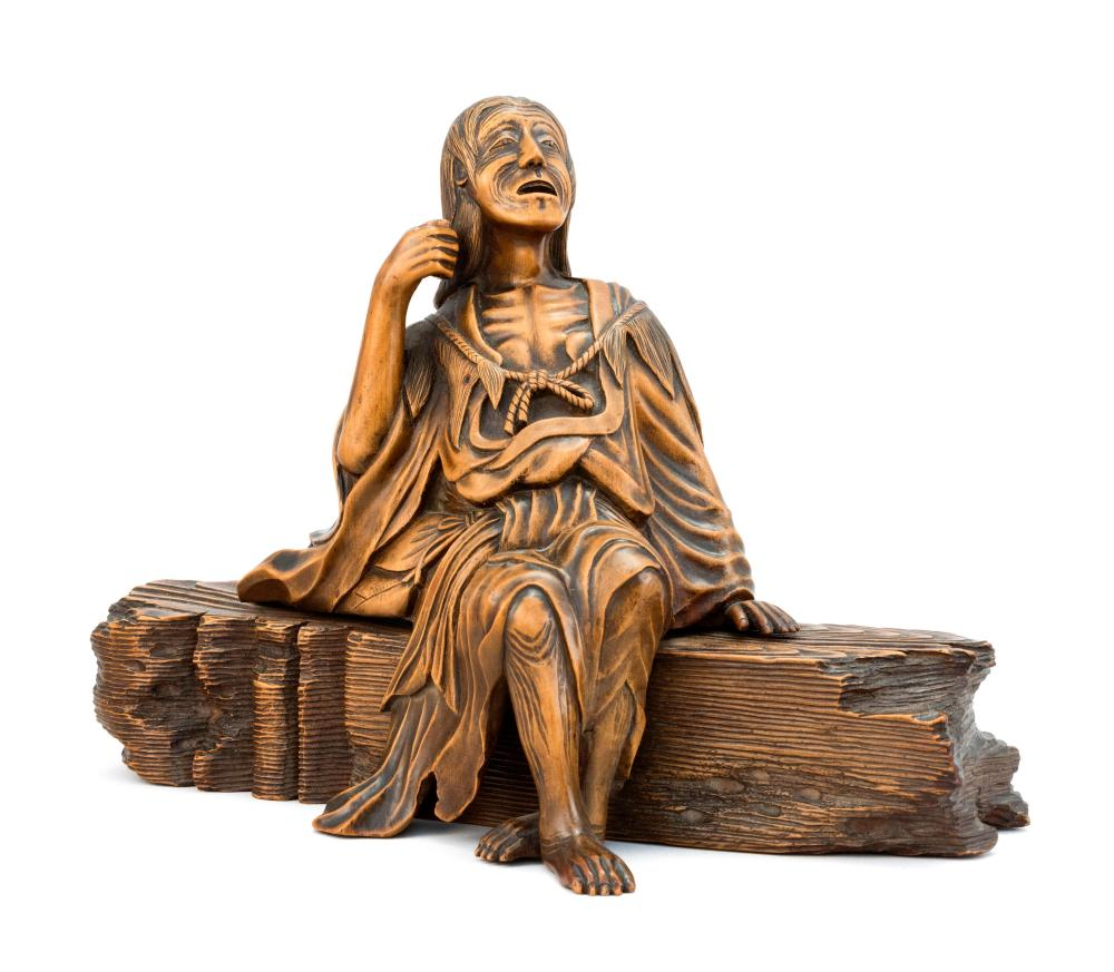 JAPANESE CARVED WOOD FIGURE Depicting a woman seated on a fallen sign post. Length 9.5