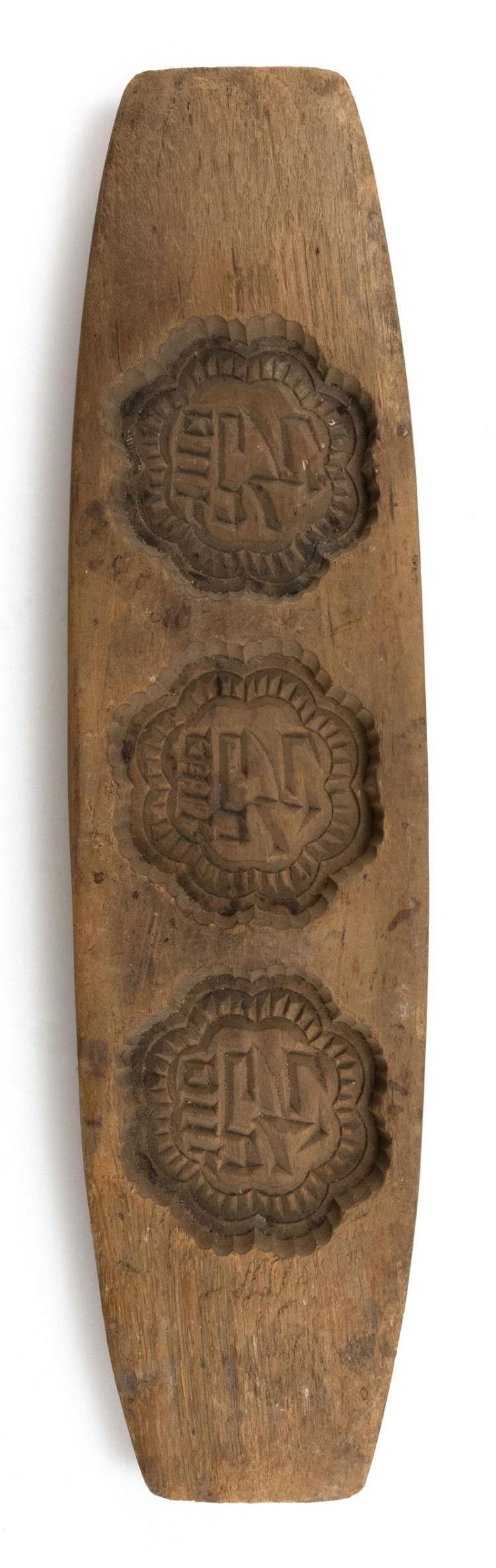 CHINESE ELMWOOD RICE CAKE MOLD In rectangular form. With three floriform sections carved with calligraphy. Length 12