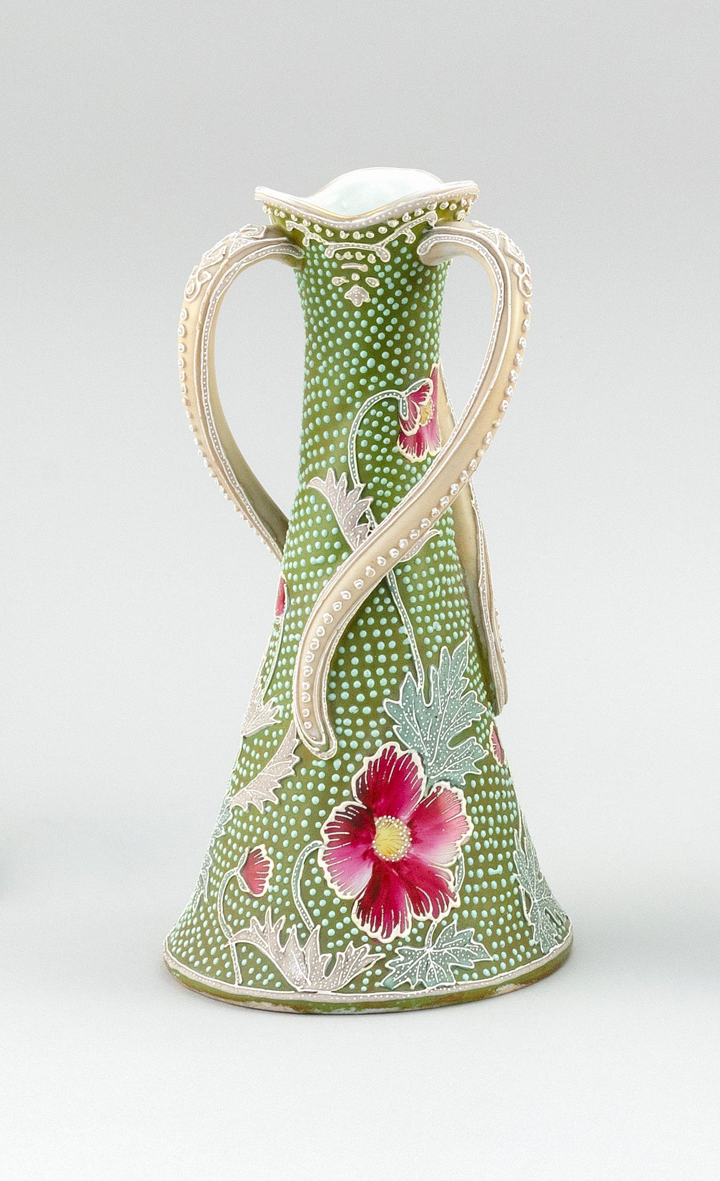 "MORIAGE NIPPON PORCELAIN VASE Conical, with three twisting handles and a floral design. Spotted with jewel-like markings. Height 10""."