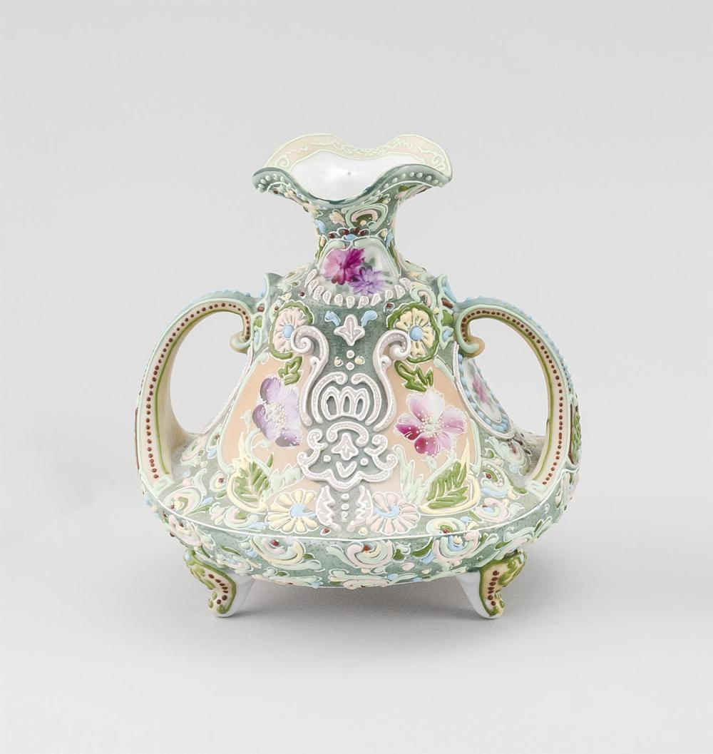 MORIAGE NIPPON PORCELAIN FOOTED VASE In bell form, with tripod base, crescent-shaped handles and floral decoration. Height 6.75