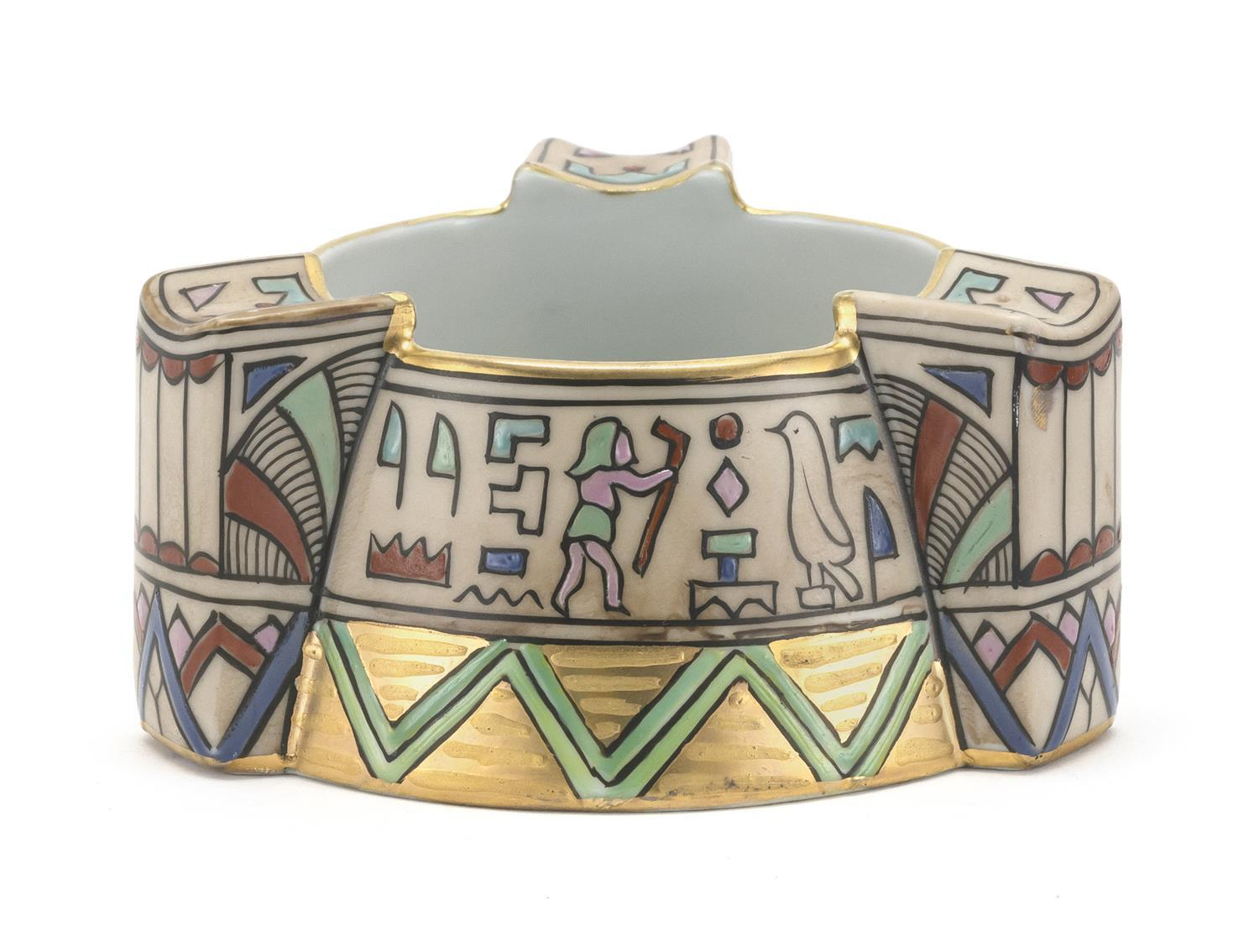 """NIPPON PORCELAIN ASHTRAY Circular, with three handles and decoration of Egyptian motifs. Diameter 4.5""""."""