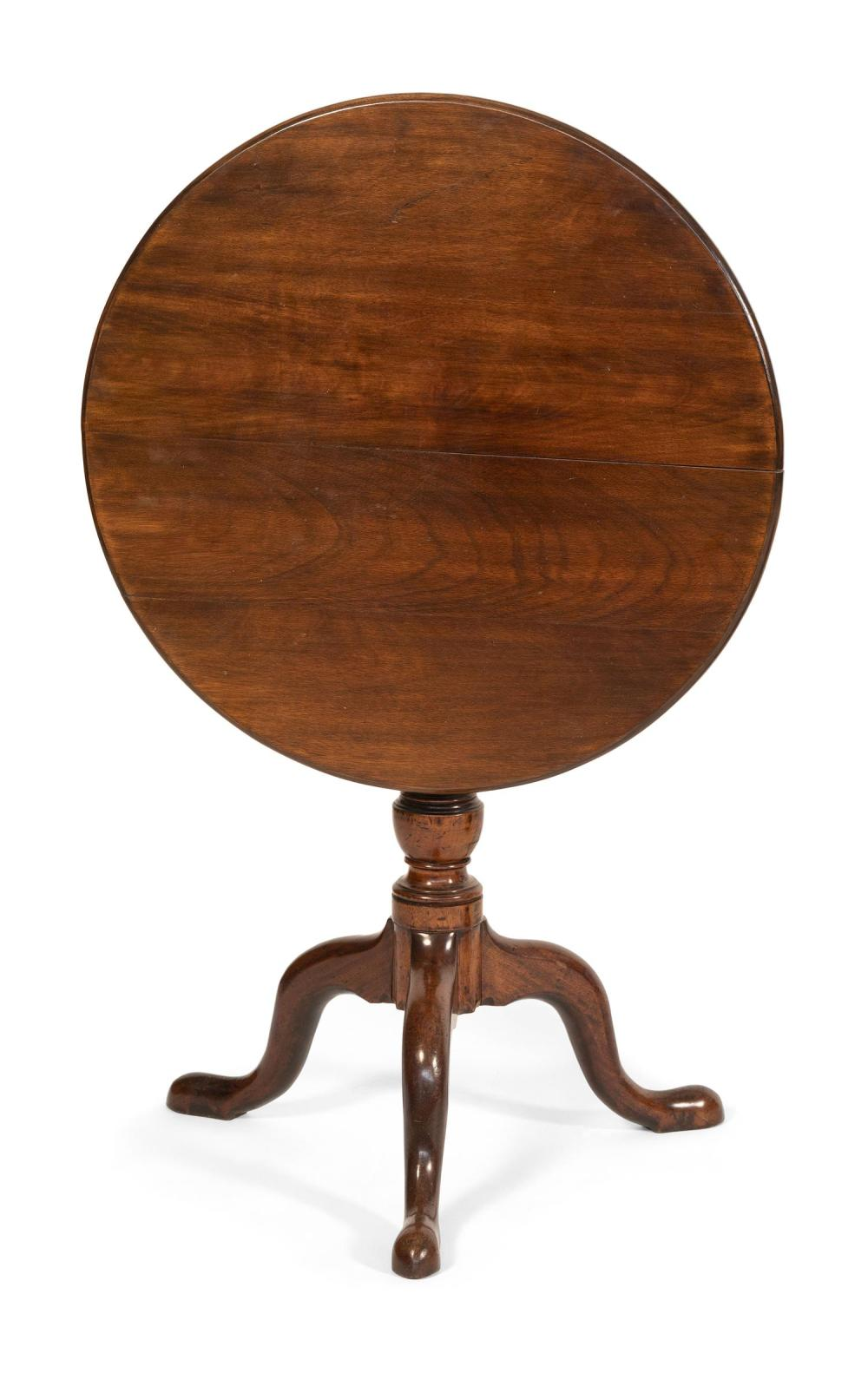 GEORGE II TILT-TOP TEA TABLE In mahogany. Circular top with birdcage mounts. Turned pedestal raised on cabriole legs ending in bold...