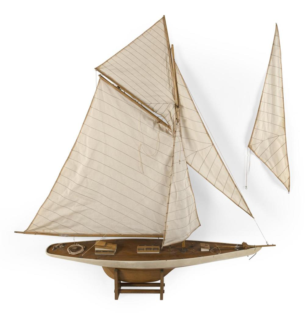 """POND MODEL OF A SAILING SLOOP With white-painted hull and hand-sewn sails. Displayed on a wooden stand. Height on stand 47"""". Length..."""
