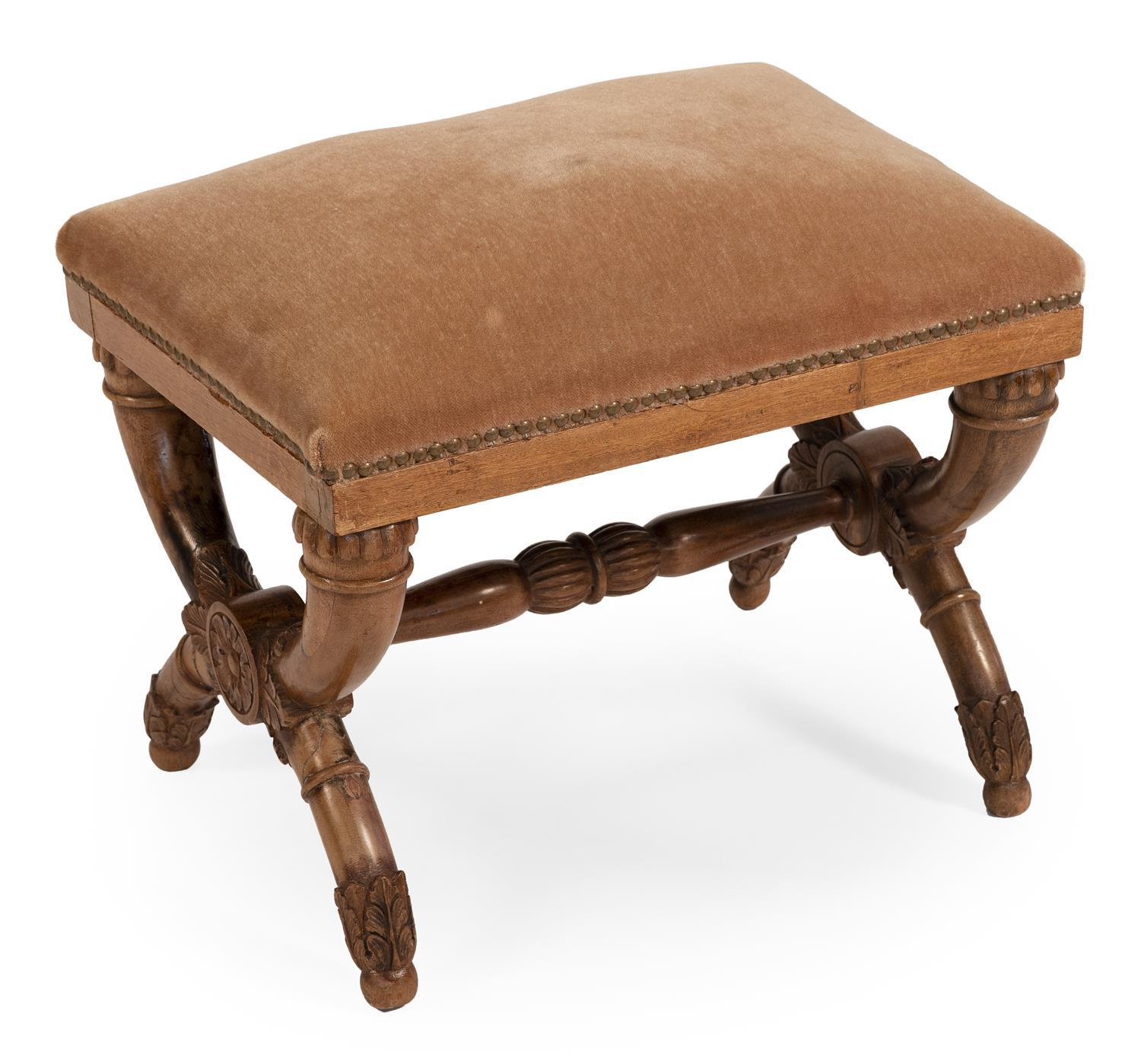 CONTINENTAL FOOTSTOOL In fruitwood. Tan velvet upholstered cushion affixed with brass studs. Acanthus-carved X-form legs joined with...