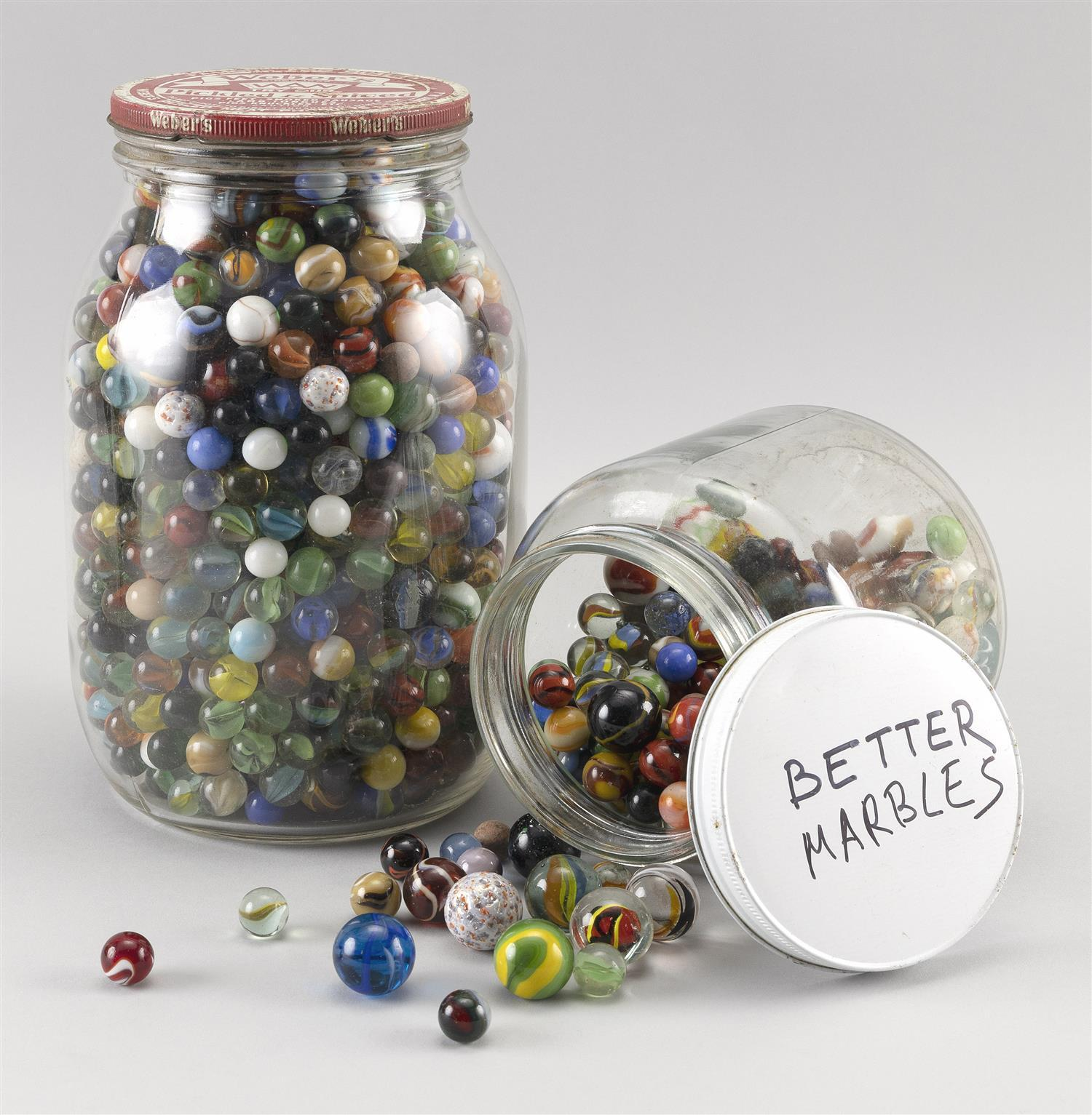 TWO PICKLE JARS CONTAINING MARBLES Mostly glass marbles but includes a few clay varieties. Various sizes and patterns. Jar heights 6...