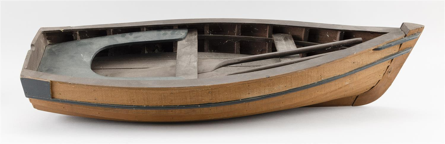 """WOODEN MODEL OF A SKIFF Painted brown and green. Includes two oars. Height 5.5"""". Length 28"""". Width 10""""."""