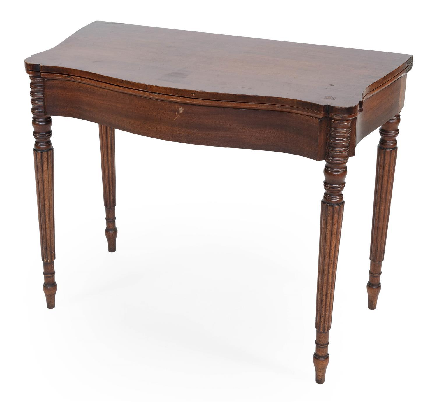 "SHERATON CARD TABLE In mahogany, with a serpentine front and tapered and reeded legs. Height 29.5"". Width 33.75"". Depth 17.5""."