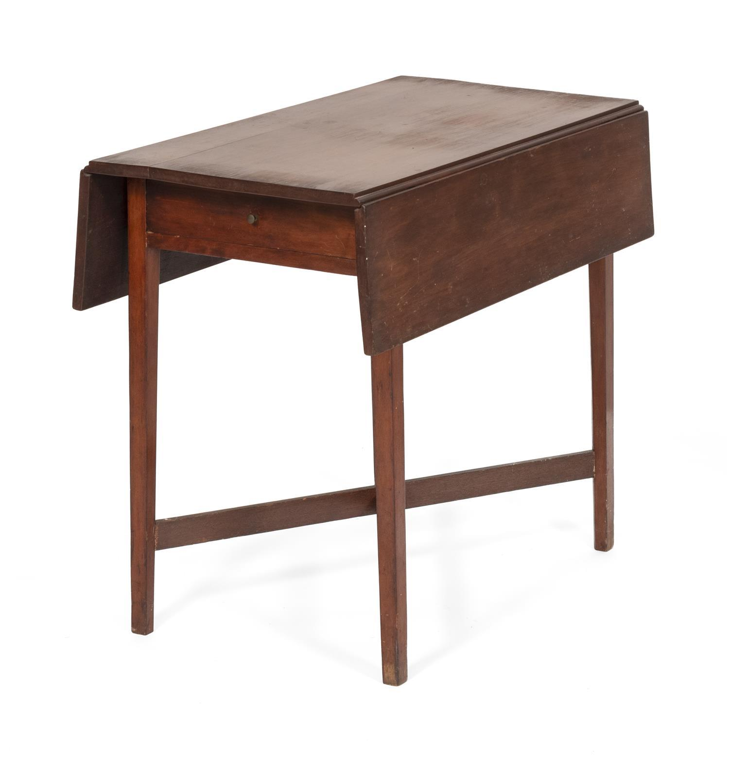 """PEMBROKE TABLE In mahogany. Drawer with a circular brass pull. Square tapered legs joined with a cross-stretcher. Height 28.5"""". Width.."""