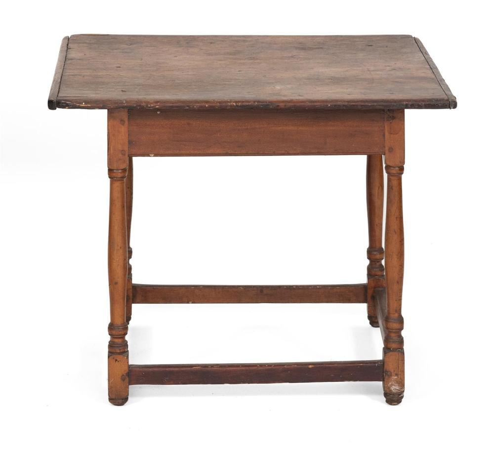 TAVERN TABLE In pine, under an old brown finish. Breadboard ends. Stretcher base with turned legs ending in button feet. Height 23.5...