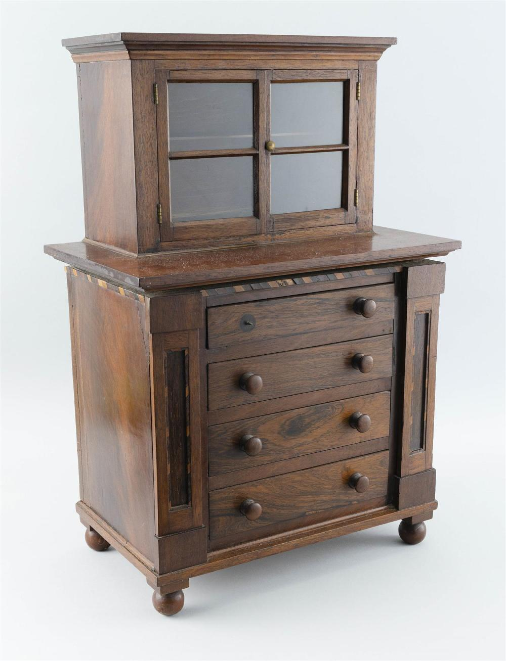 CHILD-SIZE TWO-PART CUPBOARD In mahogany and mahogany veneer. Upper case with a shaped cornice over two glass-paneled doors enclosin...