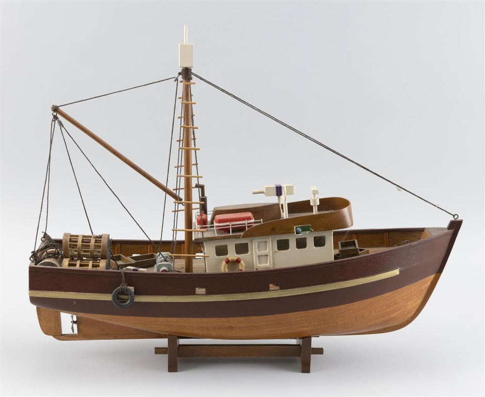 "HANDMADE MODEL OF A FISHING BOAT Detailed with traps, buoys, bumpers, etc. Affixed to a wooden cradle. Total height 14.5"". Length 17""."