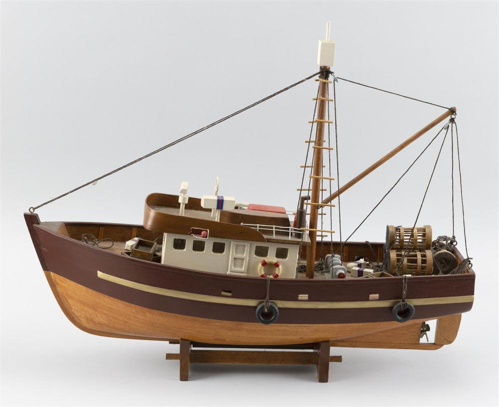 HANDMADE MODEL OF A FISHING BOAT Detailed with traps, buoys, bumpers, etc. Affixed to a wooden cradle. Total height 14.5